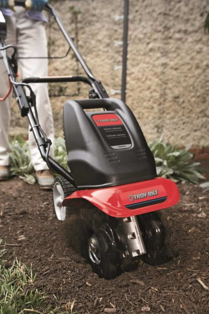 Woman using the Troy-Bilt front-tine electric tiller in the garden