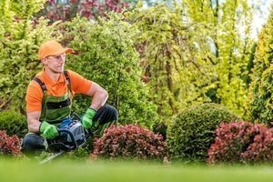 Man wearing safety gear - hat, goggles, gloves and coveralls - while holding a hedge trimmer.