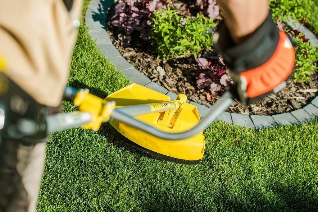 string trimmer cutting taller grass around edge of garden