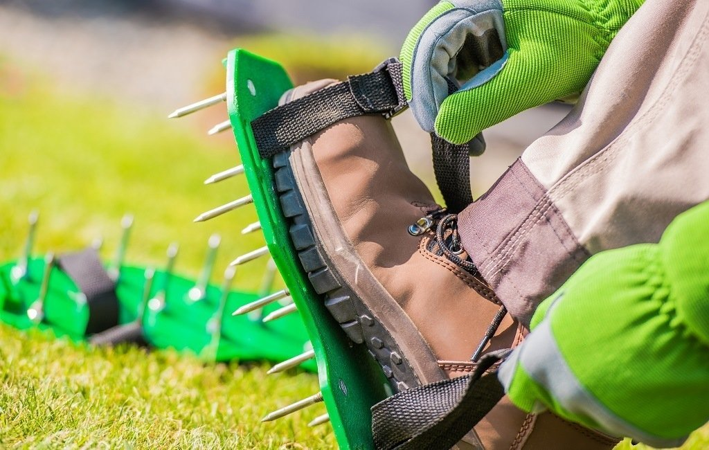 man putting on spiked shoes to aerate the lawn