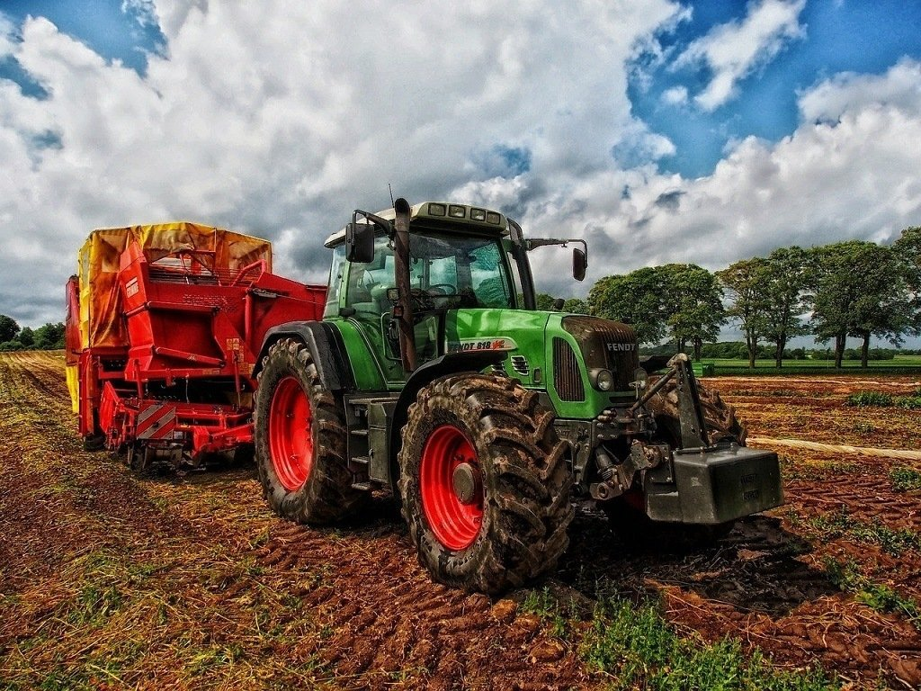 green tractor working in the fields