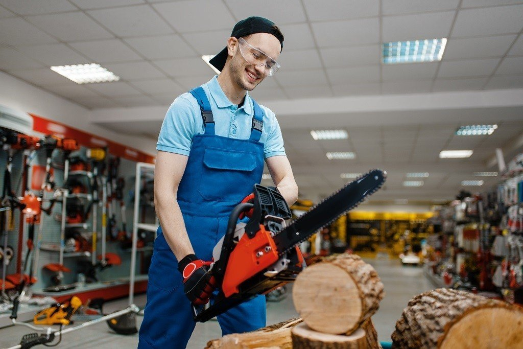 employee cutting a log inside a home improvement store to demonstrate how to use a chainsaw
