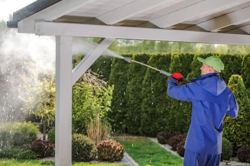 power washing the roof of a garden trellis