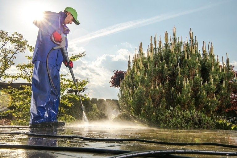 using a pressure washer to clean outdoor working areas