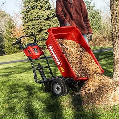 Shapper wheelbarrow dumping woodchips in the backyard with the easy release lever