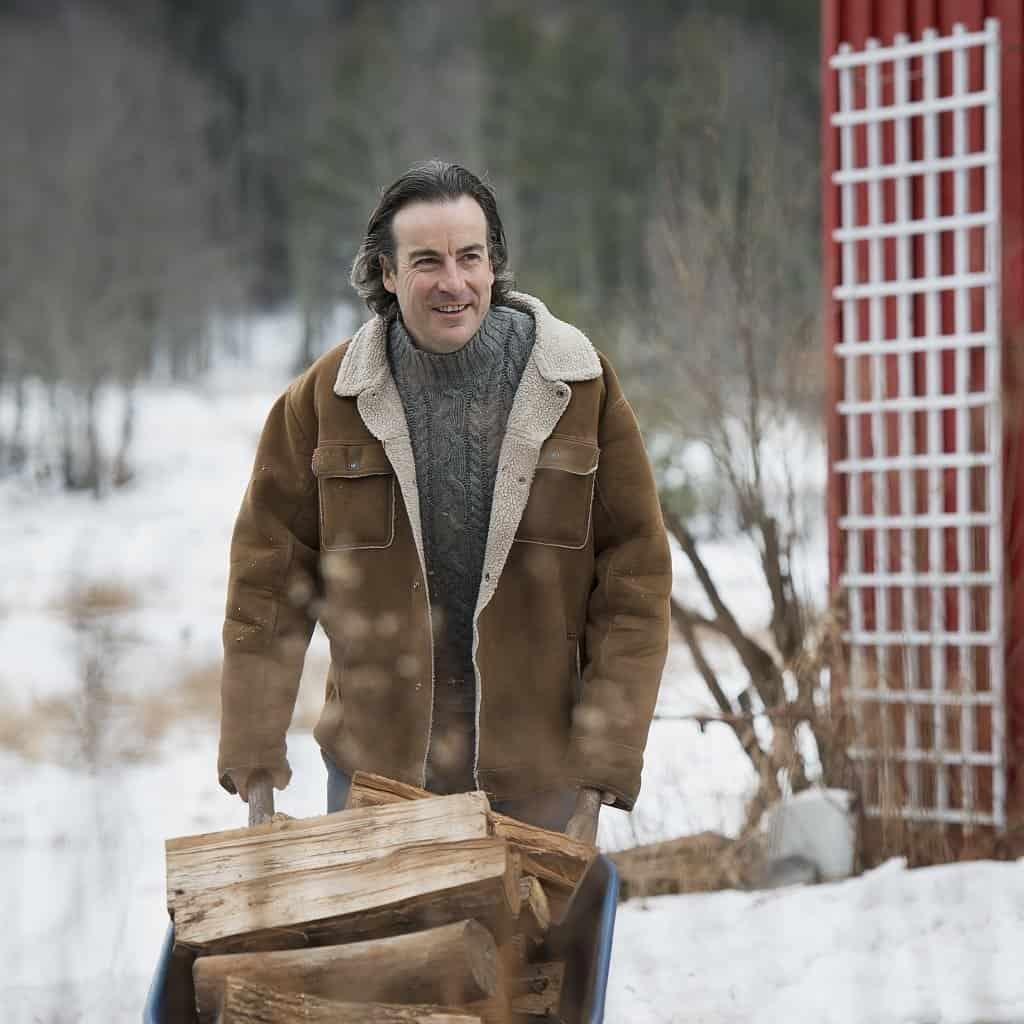 man hauling firewood in a wheelbarrow