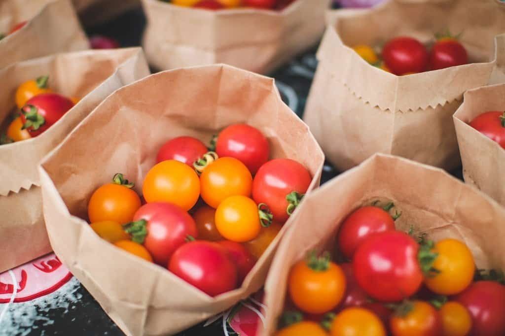 bags of heirloom tomatoes for sale at a market