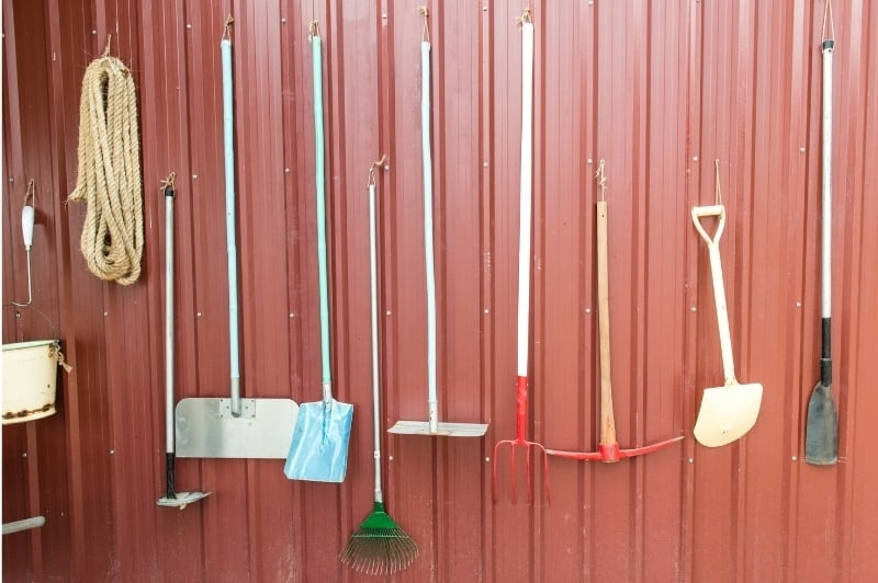 farm hand tools neatly organized and hanging on a red barn
