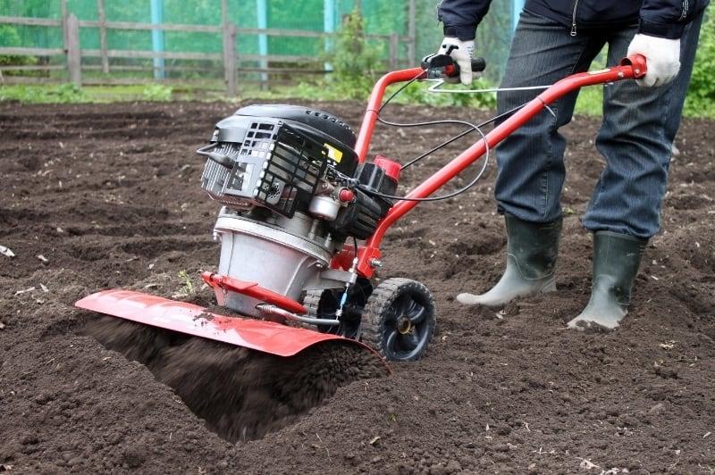 man preparing a new garden area with rototiller