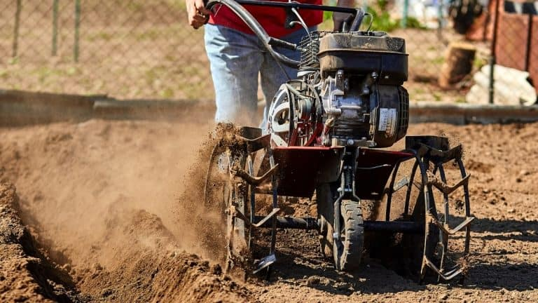 Man with large rototiller working creating a new garden bed with patches of brown earth all around